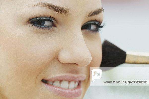 Portrait einer jungen Frau Make-up mit einem Make-up Pinsel anwenden