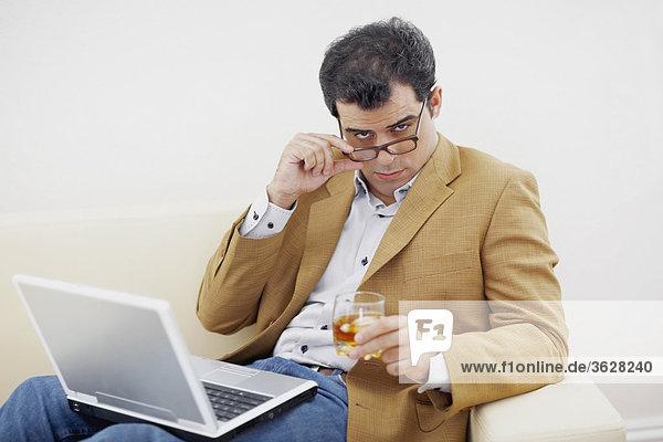 Porträt eines Mitte Erwachsenen Mannes hält ein Glas Wein und Blick auf seine Brillen