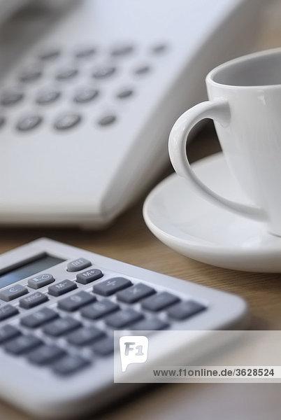 Nahaufnahme Taschenrechner mit einer Teetasse
