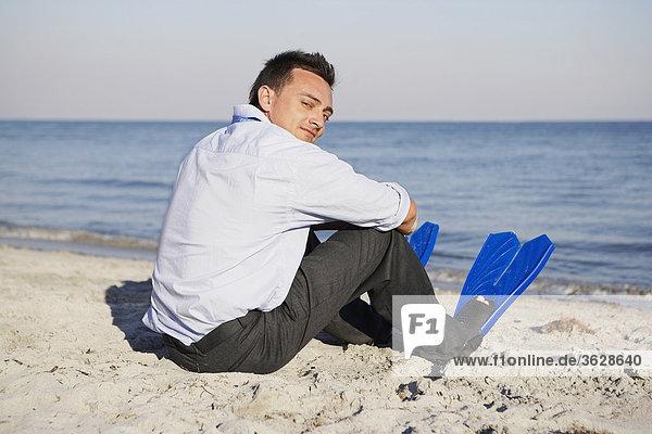 Rückansicht eines jungen Mannes am Strand sitzen