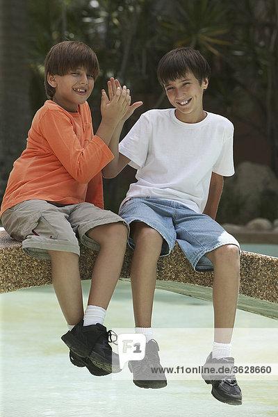 Porträt von zwei jungen sitzen auf einer Fußgängerbrücke in einem Teich
