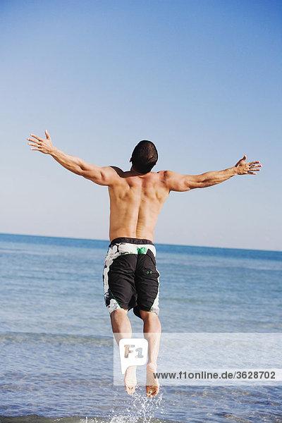 Mann Strand springen Mittelpunkt Rückansicht Ansicht Arme ausbreiten Arme ausstrecken strecken Erwachsener