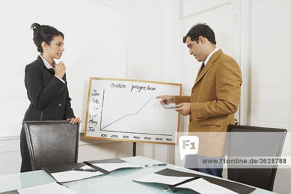 Vorführen einer Präsentation Graph auf eine geschäftsfrau kaufmann