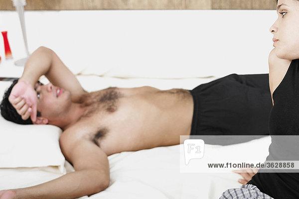 Nahaufnahme einer jungen Frau Blick auf einen jungen Mann auf dem Bett liegend