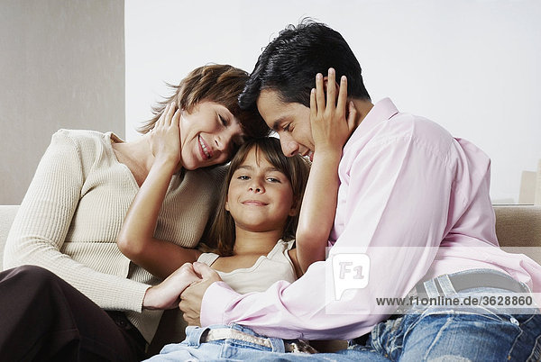 Paar sitzen mit ihrer Tochter und lächelnd
