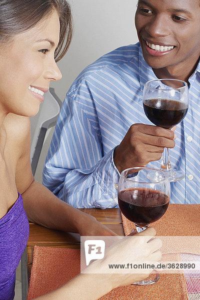 Nahaufnahme eines jungen Paares sitzen und halten Gläser Wein