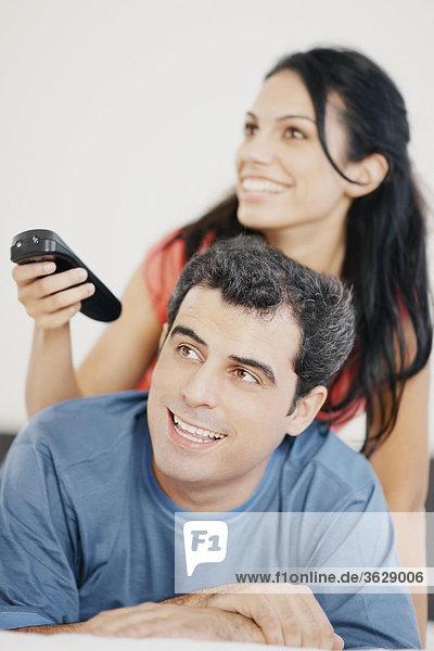 Nahaufnahme einer jungen Frau und ein Mitte Erwachsenen Mann vor dem Fernseher und lächelnd