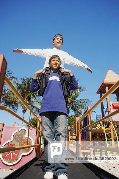Untersicht of ein Teenager mit seinem Bruder auf der Schulter