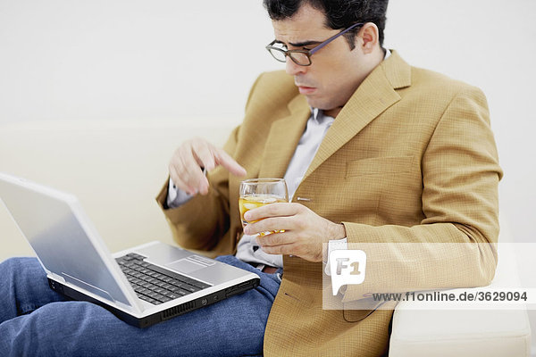 Close-up of a mid adult man looking at a laptop and holding a glass of wine