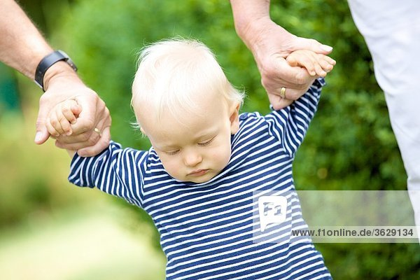 Großeltern gehen Hand in Hand mit Kleinkind