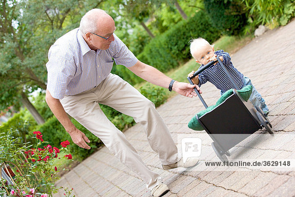 Großvater und Kleinkind mit Puppenwagen im Freien