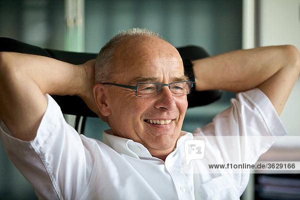 Lächelnder Senior im Arbeitszimmer Heimarbeitsplatz