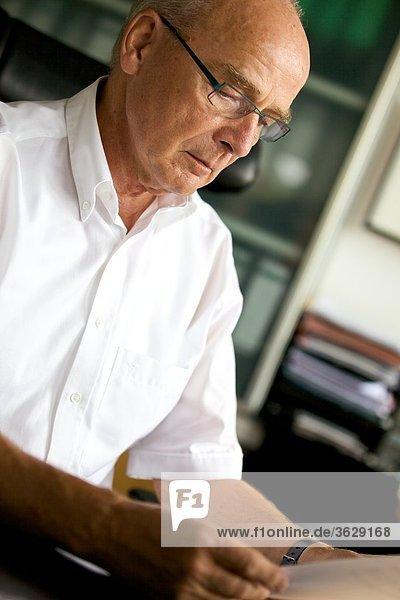 Senior liest Dokument am Schreibtisch