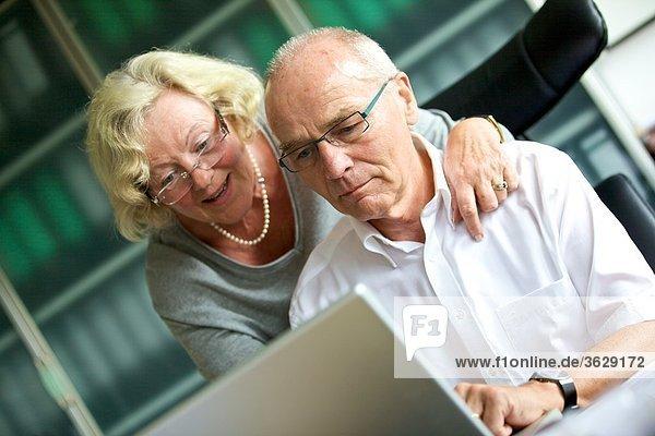 Seniorin umarmt Mann am Schreibtisch