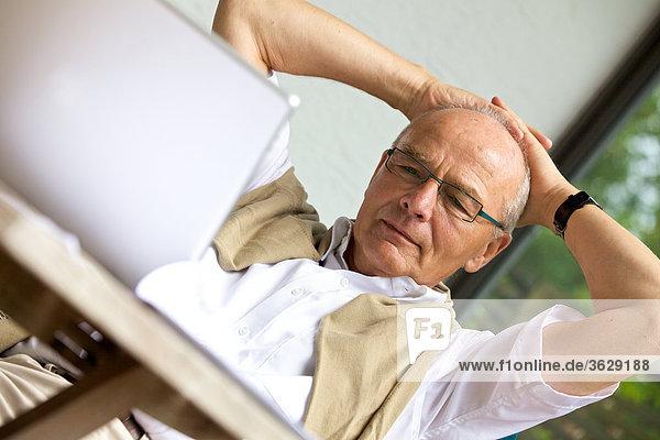 Senior benutzt Laptop auf der Terrasse