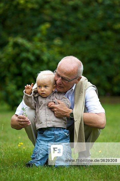 Großvater und Kleinkind auf einer Wiese
