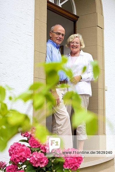 Glückliches Seniorenpaar an der Eingangstür