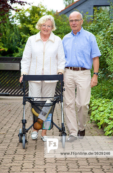 Seniorenpaar mit Rollator erledigt Einkäufe
