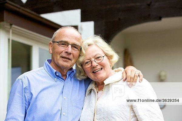 Glückliches Seniorenpaar umarmt sich vor Wohnhaus  Portrait