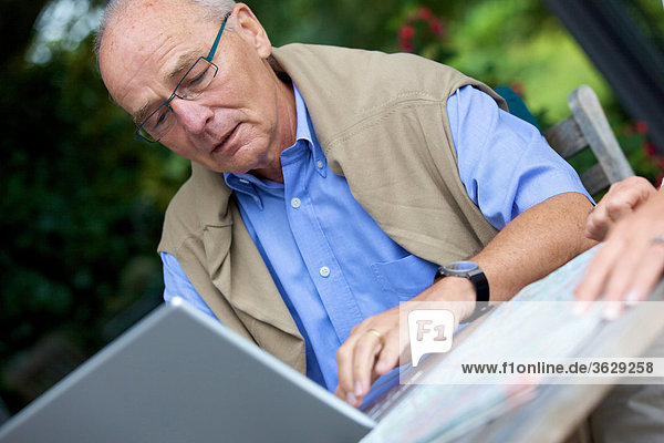Senior mit Laptop und Straßenkarte  close-up
