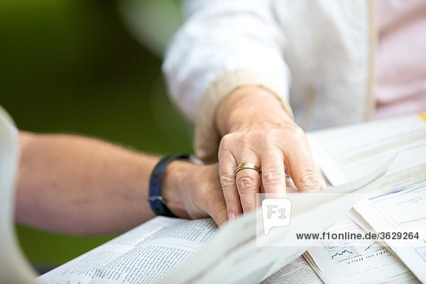 Seniorenpaar liest Hand in Hand Zeitung  close-up