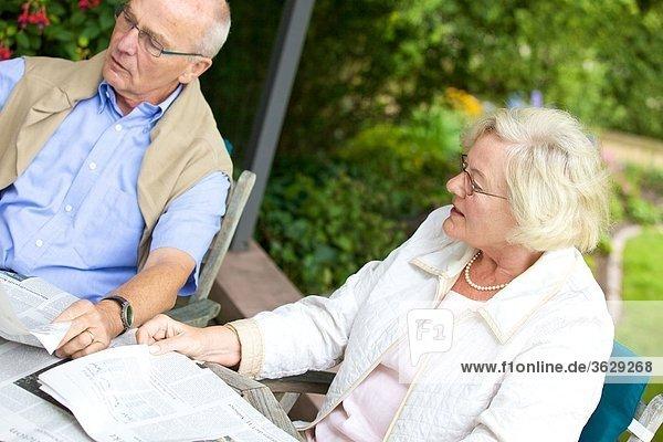 Seniorenpaar liest Zeitung auf der Terrasse