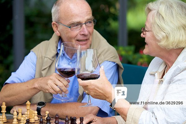 Seniorenpaar auf der Terrasse spielt Schach und trinkt Rotwein