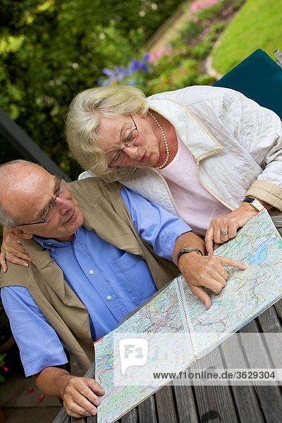 Seniorenpaar auf der Terrasse schaut auf Straßenkarte