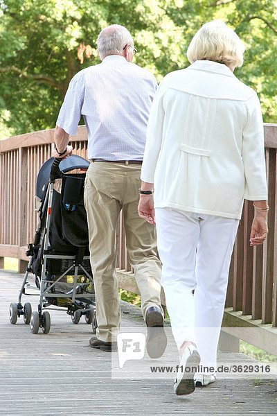 Großeltern gehen mit Enkelsohn im Kinderwagen spazieren