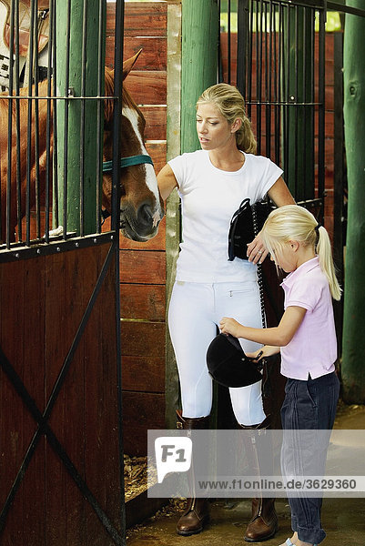 Mid adult woman and her daughter standing in a stable