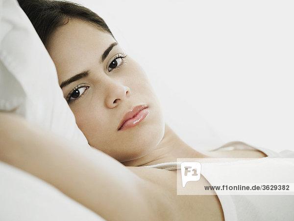 Portrait einer jungen Frau auf dem Rücken liegend
