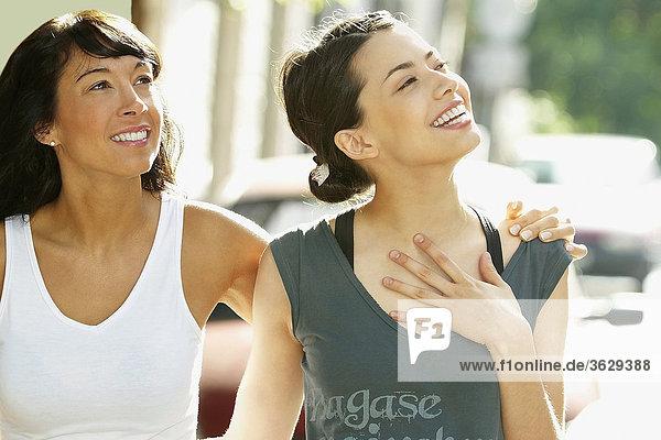 Nahaufnahme einer jungen Frau stehen und mit einer Mitte erwachsen Frau lächelnd