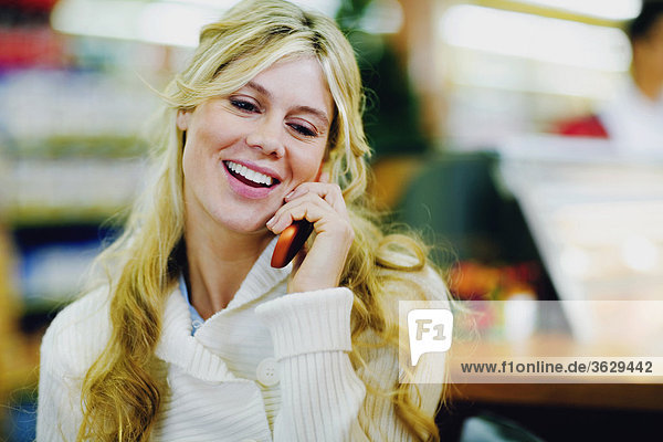 Close-up of a young woman smiling and talking on a mobile phone