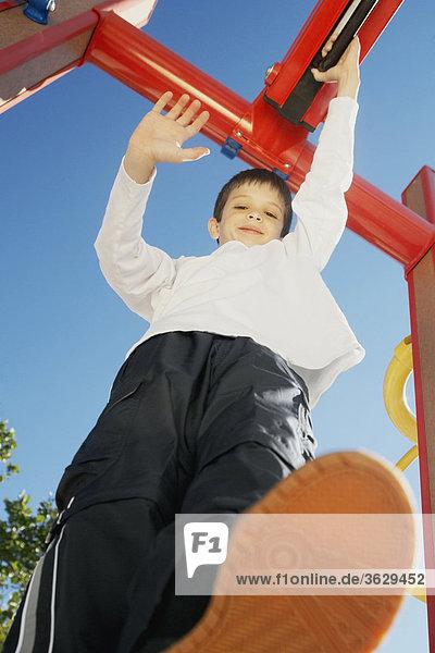 Bildnis eines Knaben lächelnd und Stand auf einem Klettergerüst mit seiner hand