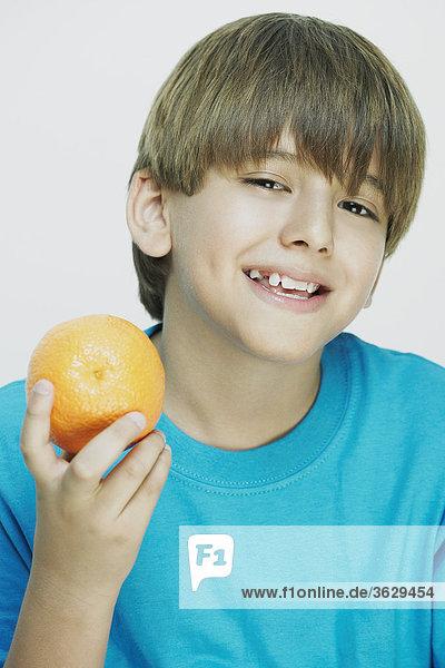 Nahaufnahme eines jungen hält eine Orange und lächelnd
