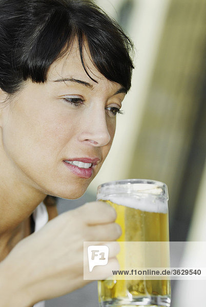 Close-up of a mid adult woman holding a glass of beer