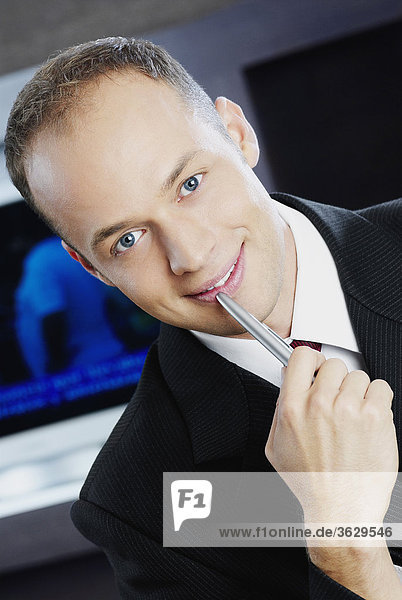 Portrait of a businessman holding a pen and smiling