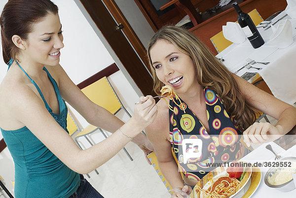 Junge Frau Fütterung einer anderen Nudeln