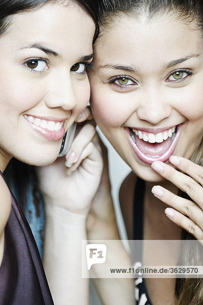 Portrait of two young women listening to a mobile phone and smiling