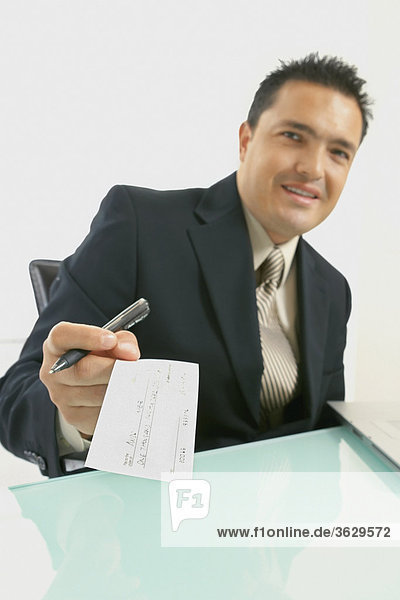 Portrait of a businessman smiling with a pen and a check