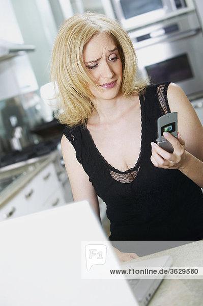 Mitte erwachsen frau hält ein Mobiltelefon und suchen traurig