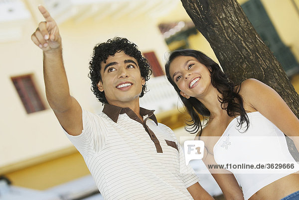 Close-up of a teenage boy pointing to a young woman