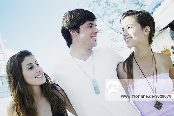 Close-up of a young man and two young women smiling