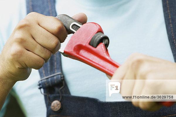 Nahaufnahme eines Mannes mit einem verstellbaren Schraubenschlüssel