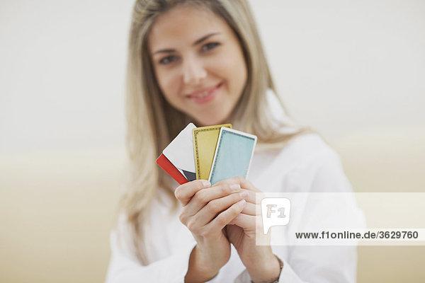 Portrait einer Mitte erwachsen frau hält Kreditkarten und lächelnd