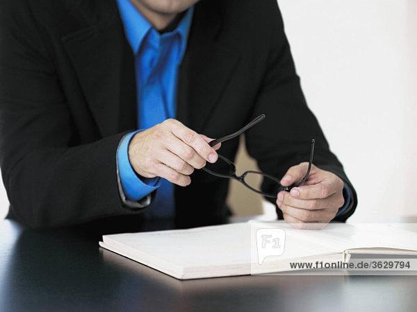 Mitte Schnittansicht eines Kaufmanns Sitzung an einem Tisch und hält Brillen