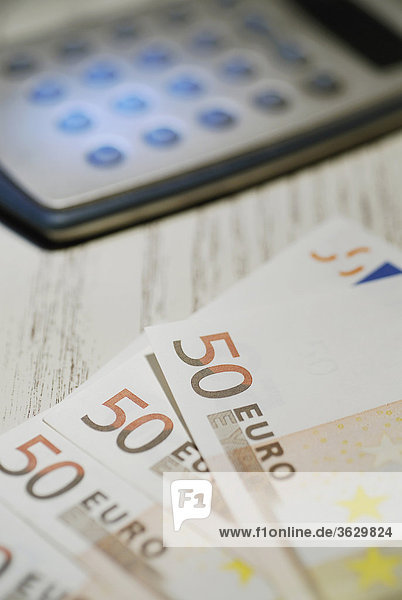 Close-up of fifty Euro banknotes and a calculator