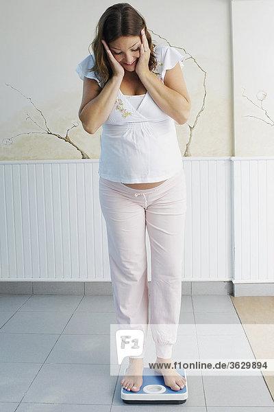 Schwangere junge Frau auf einer Waage