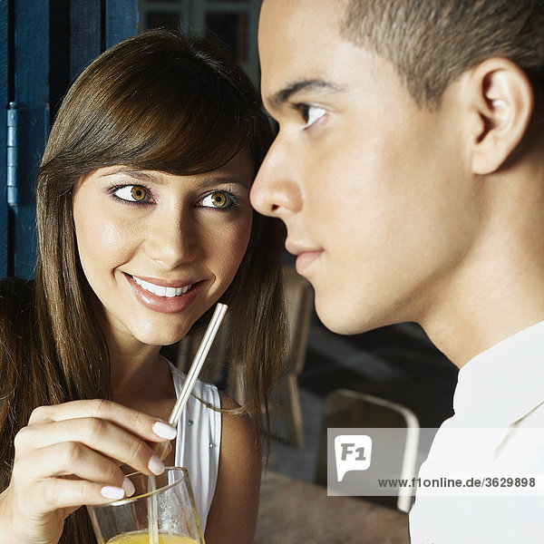 Close-up of a young woman offering a glass of juice to a young man