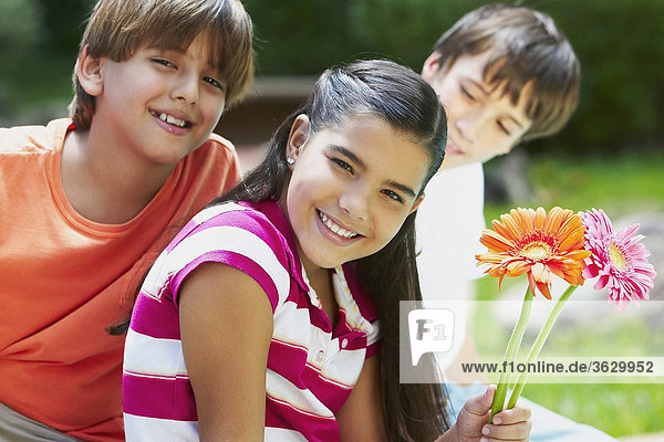 Mädchenbildnis hält Blumen und lächelnd mit ihren Freunden